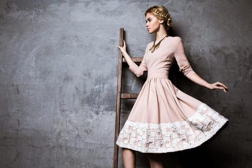 ベージュのワンピースドレスにゴールドのアクセサリーをつけて華やかなスタイル