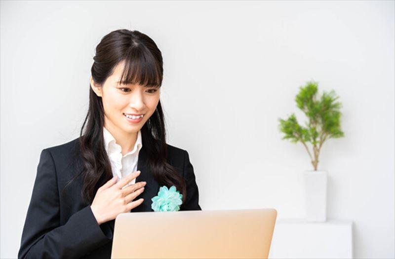 スーツを着てパソコンの前に座る女性