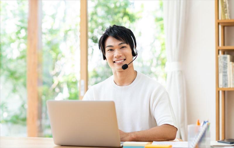 ヘッドフォンをつけてパソコンの前でほほ笑む若い男性