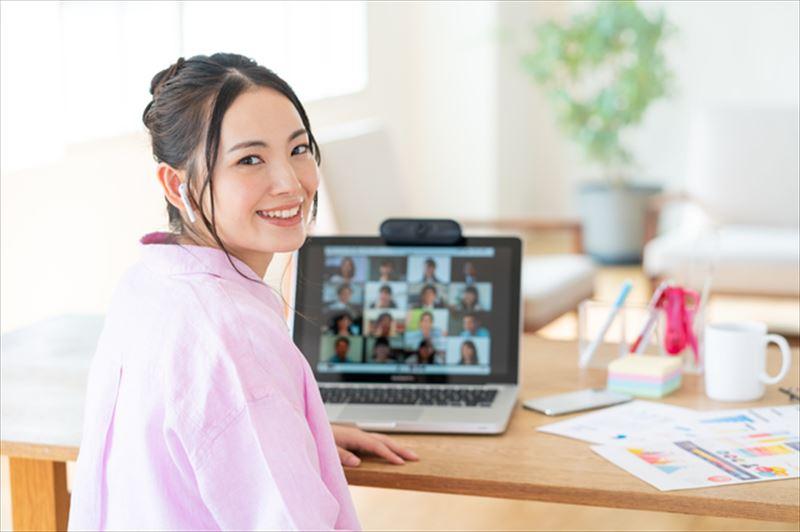 パソコンの前でほほ笑む女性