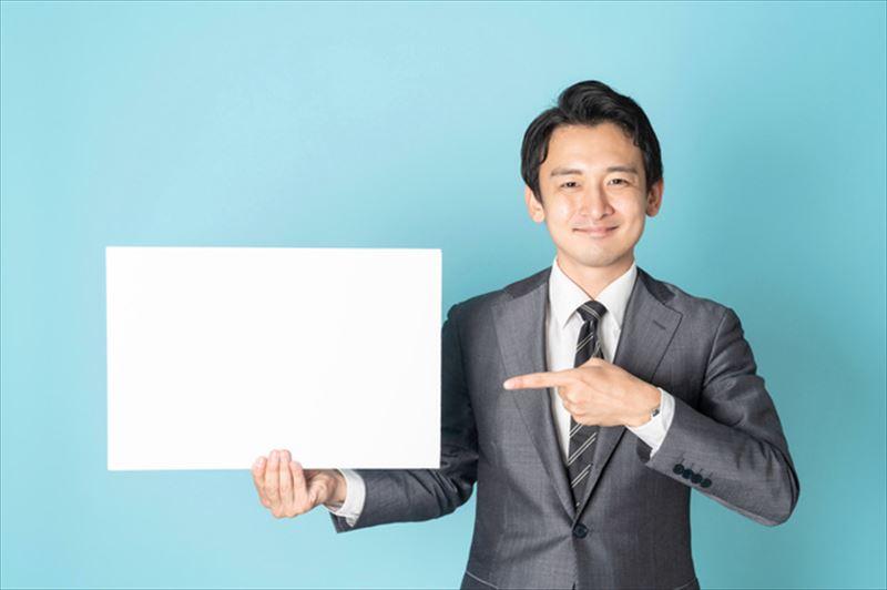 白いボードを持ってほほ笑む男性