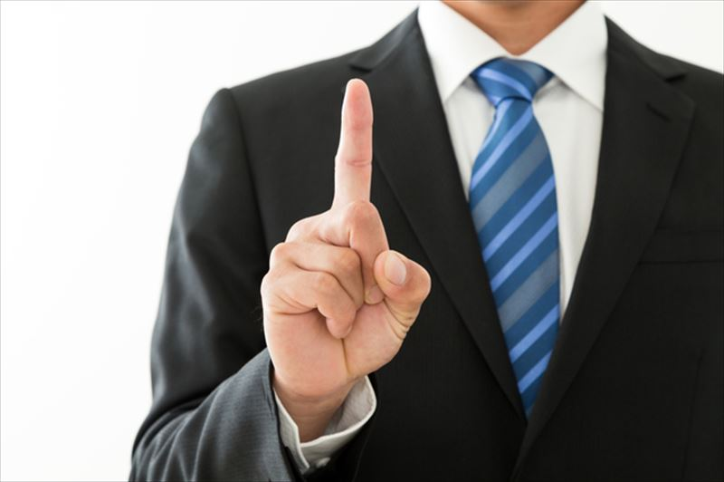 人差し指をあげる男性のアップ